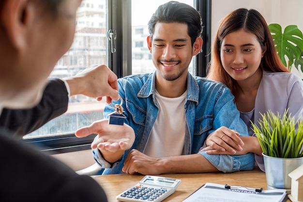 Lato posteriore della mano rappresentante di vendita offre la catena chiave di casa alla giovane coppia asiatica