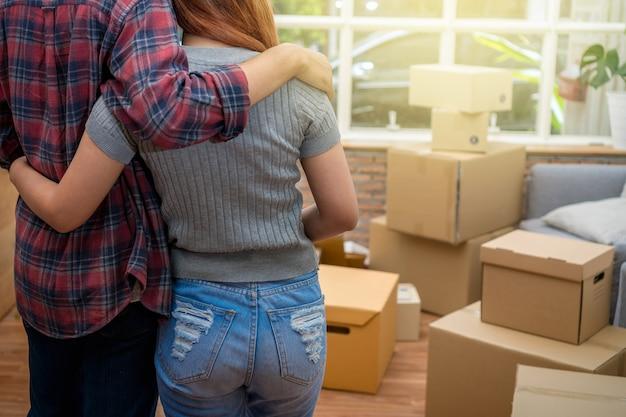 Lato posteriore delle giovani coppie asiatiche che abbracciano insieme la grande scatola di cartone e sofà