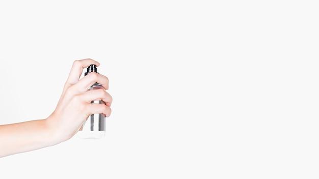 Latta di spruzzo umana della holding della mano sopra priorità bassa bianca