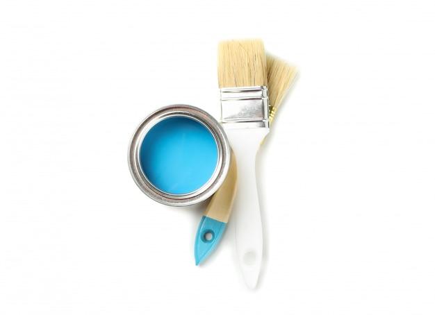 Latta e spazzole di vernice isolate su superficie bianca