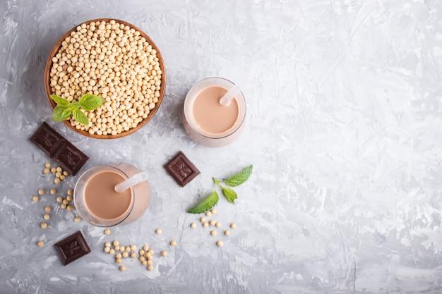 Latte al latte di soia non caseario biologico in vetro e piatto di legno con semi di soia su un cemento grigio.