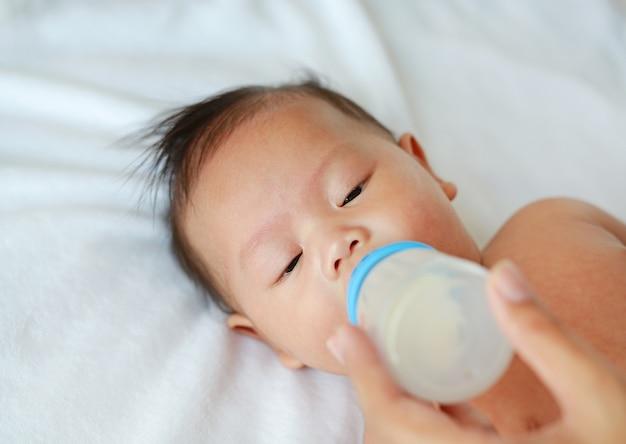 Latte alimentare infantile del bambino asiatico dalla bottiglia