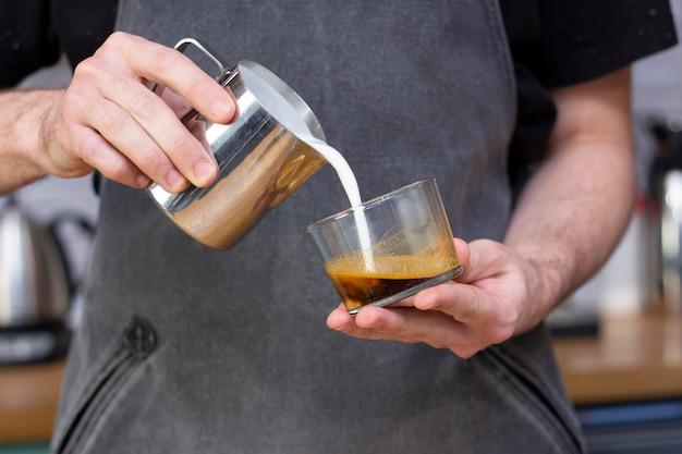 Latte art. l'arte di disegnare sul caffè. il barista produce latte art latte da una brocca