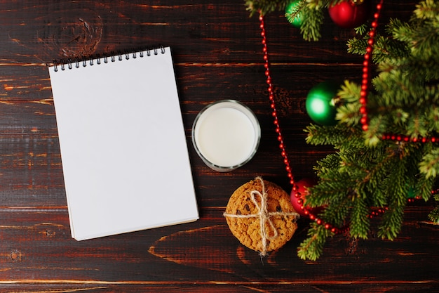 Latte, biscotti e una lista dei desideri sotto l'albero di natale. l'arrivo di babbo natale.