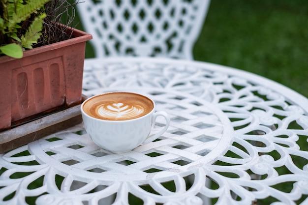 Latte caldo del caffè con schiuma a forma di fiore in tazza bianca sulla retro tavola