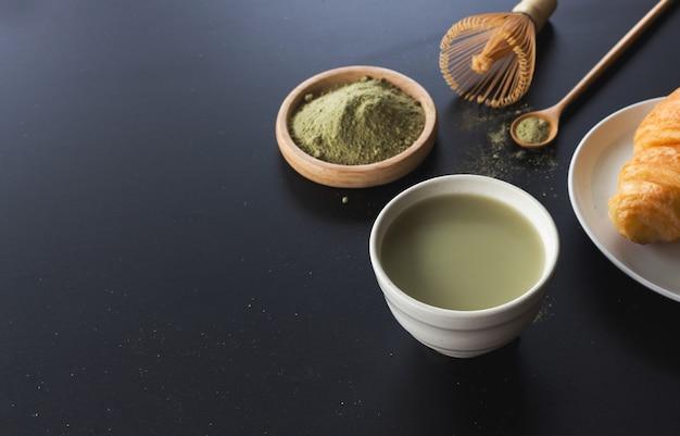 Latte del tè verde di matcha sulla tavola nera