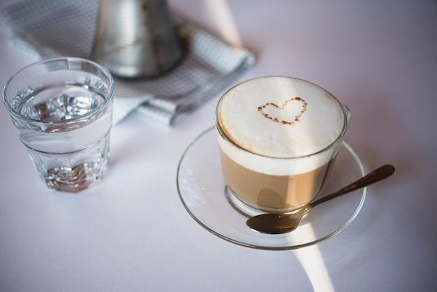 Latte della tazza di caffè del primo piano con bicchiere d'acqua