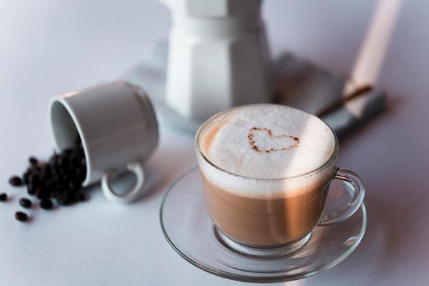 Latte della tazza di caffè del primo piano con il bollitore