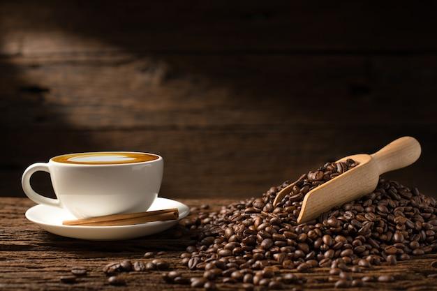 Latte della tazza di caffè e chicchi di caffè su vecchio fondo di legno