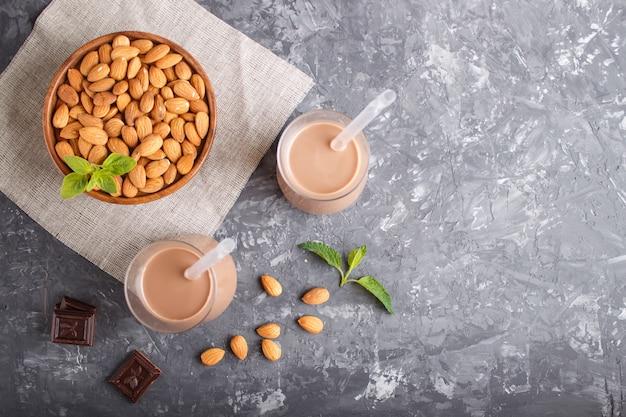 Latte di cioccolato al latte non pastorizzato biologico in vetro e piatto di legno con noci di mandorle su un cemento nero.