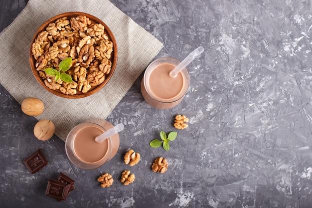 Latte di cioccolato biologico alle noci non caseario in vetro e piatto di legno