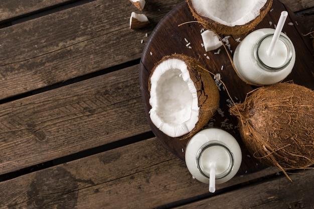 Latte di cocco in bottiglie sulla tavola di legno. bevanda salutare vegana non casearia. concetto di mangiare sano