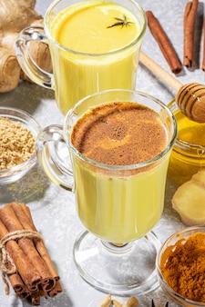 Latte di curcuma ayurvedico. due bicchieri per vin brulè con latte dorato con ingredienti su grigio chiaro.