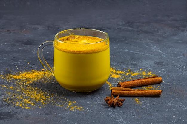 Latte di curcuma indiano tradizionale in tazza di vetro con anice stellato e cannella