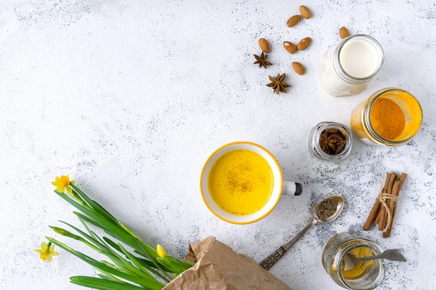 Latte di curcuma vegano in una tazza, latte di mandorle, miele, spezie, bouquet di duffodils gialli, vista dall'alto