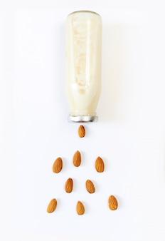 Latte di mandorla e semi di mandorla sopra bianco