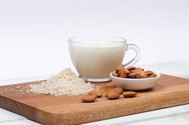 Latte di mandorla in tazza con farina di mandorle e noci su sfondo bianco