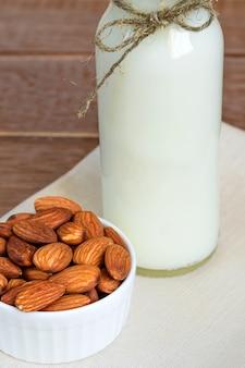 Latte di mandorle fatto in casa in una bottiglia e noci in ciotola di porcellana bianca