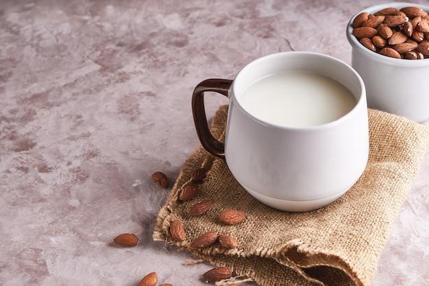 Latte di mandorle fatto in casa in una tazza e bottiglia, chicchi di mandorle su superficie rustica. cibi e bevande alternativi.