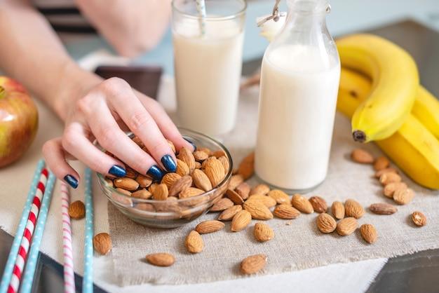 Latte di mandorle in un bicchiere tazza e frutta con mandorle sparse sul tavolo della cucina. dieta prodotto vegetariano sano