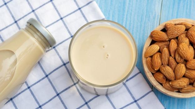 Latte di mandorle su un tavolo di legno blu.