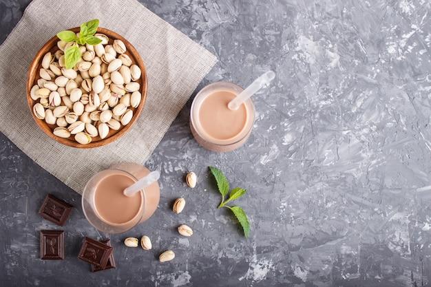 Latte di pistacchio biologico non da latte in vetro e piatto di legno con pistacchi su un cemento nero.