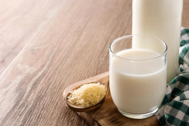 Latte di riso in vetro e bottiglia sulla tavola di legno. copia spazio