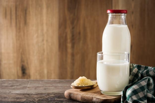 Latte di riso in vetro e bottiglia sulla tavola di legno.