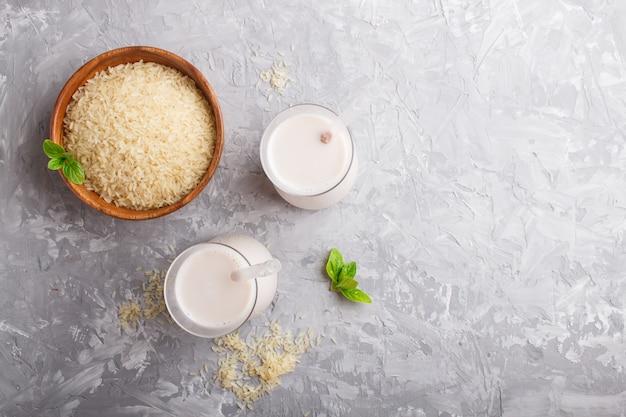 Latte di riso non caseario biologico in vetro e piatto di legno con semi di riso su un cemento grigio.