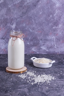 Latte di riso vegano in una bottiglia di vetro e riso in un piatto bianco su un supporto di legno su uno sfondo grigio con un tovagliolo grigio