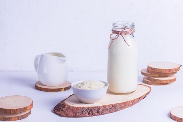 Latte di riso vegano in una bottiglia di vetro e riso in un piatto bianco su un supporto in legno su uno sfondo bianco