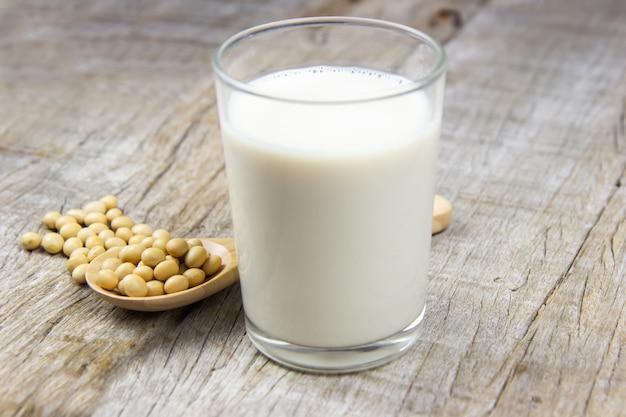 Latte di soia con soia su fondo in legno.