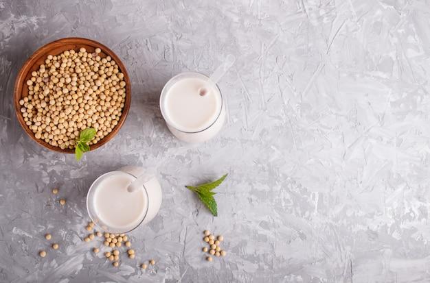 Latte di soia non caseario biologico in vetro e piatto di legno con semi di soia su un cemento grigio.