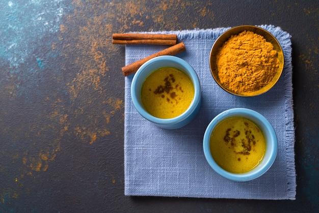 Latte dorato del latte della curcuma fatto con curcuma e altre spezie su fondo di legno.