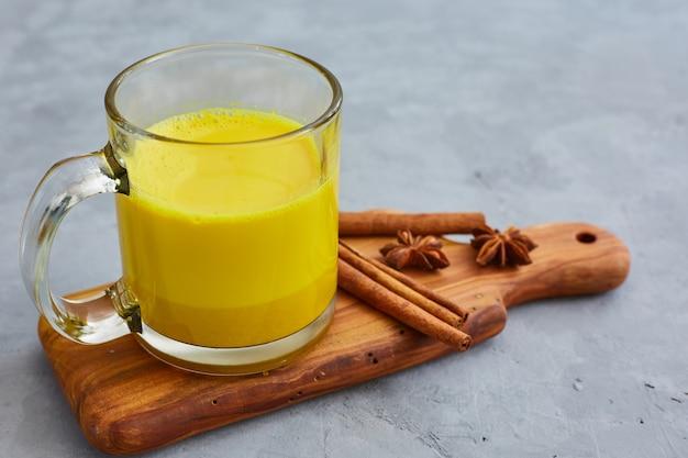 Latte dorato della curcuma della bevanda sana in tazza di vetro. tagliere di legno su una superficie di cemento grigia. anice stellato e cannella.detox tè alla curcuma e ingredienti.
