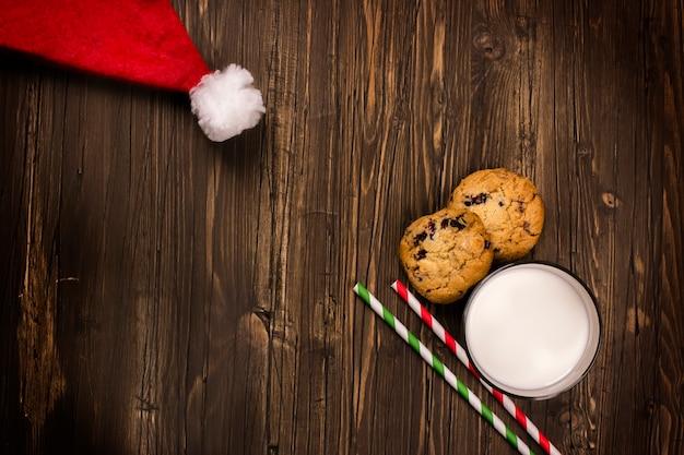 Latte e biscotti per babbo natale e cappello di babbo natale. concetto di natale, biglietto di auguri.