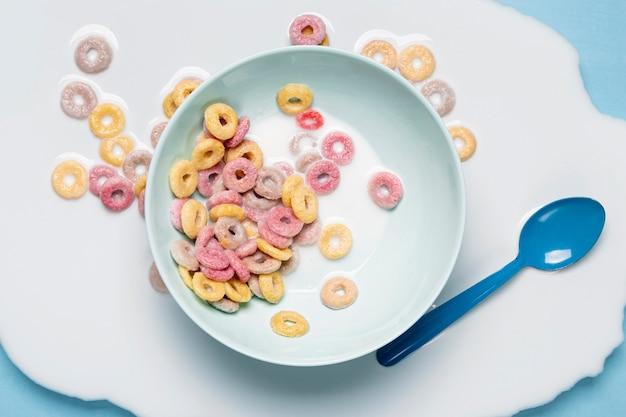 Latte e cereali versati su tutto il tavolo e cucchiaio blu