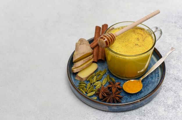 Latte e spezie di curcuma sopra. latte dorato in tazza di vetro con spezie su sfondo chiaro con spazio di copia.