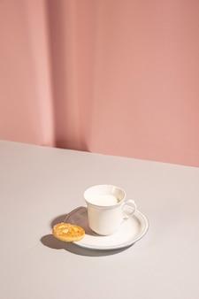 Latte fresco con biscotto dolce sul tavolo su sfondo rosa