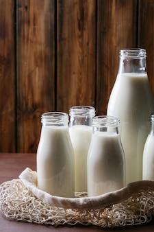 Latte fresco in diverse bottiglie di vetro
