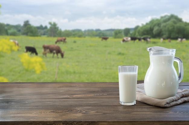 Latte fresco in vetro sulla tavola di legno scura e paesaggio vago con la mucca sul prato. mangiare sano. stile rustico.