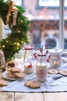 Latte in un bicchiere al tavolo vicino alla finestra, biscotti su un piatto e una corona di alberi di natale