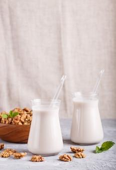 Latte organico non caseario della noce in vetro e piatto di legno con le noci su un fondo concreto grigio.