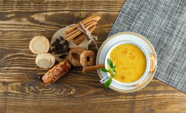 Latte piccante in una tazza con menta, biscotti, chiodi di garofano, vista dall'alto di bastoncini di cannella sul tavolo di legno