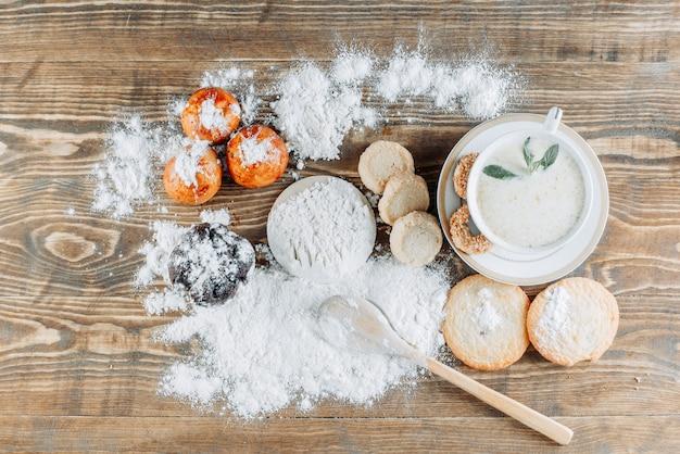 Latte speziato con menta, biscotti, cucchiaio, zucchero a velo in una tazza su superficie di legno in superficie, piatto disteso.