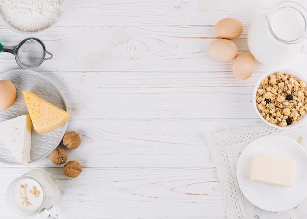 Latte; uova; ciotola di cereali; formaggio; farina e noci sul tavolo di legno bianco