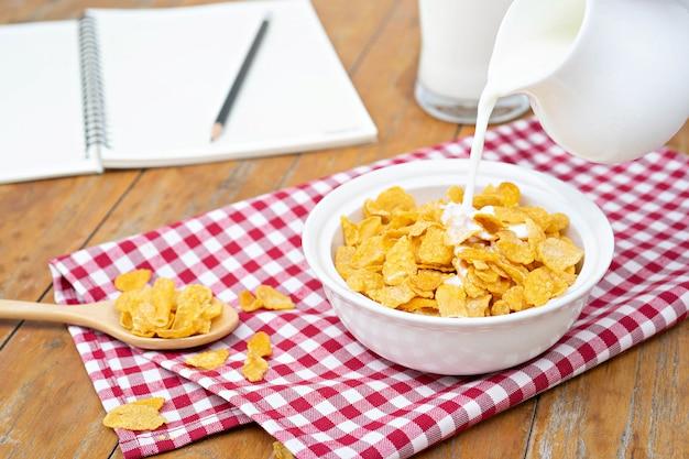 Latte versando in una ciotola di deliziosi cereali di mais.