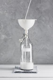 Latte versato in bottiglia con imbuto