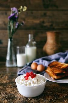 Latticini sul tavolo di legno scuro. panna acida, latte, formaggio, uova e toast
