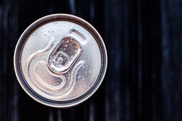 Lattina di birra con condensa su sfondo nero. lattina di alluminio da bere con gocce d'acqua, lattina di cola refrigerata, vista dall'alto. spazio testo.
